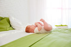 Funny baby playing with legs, while lying in bed at home Stock Photography