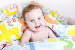 Funny baby playing peek-a-boo under colorful blanket Stock Photo