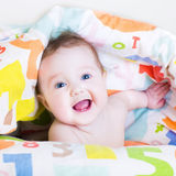 Funny baby playing peek-a-boo under a colorful blanket Stock Photo