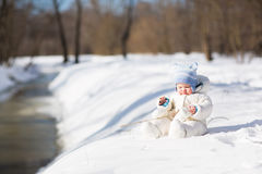 Funny baby playing at a snowy river Royalty Free Stock Photography