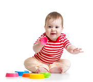 Funny baby playing with toys while sitting on floor, Royalty Free Stock Photography