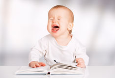 Funny baby reading a book and cries Stock Images