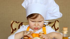 Funny baby in the role of cook kneads dough stock video footage