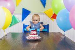 Funny baby's first birthday. Funny baby girl celebrating her first birthday Royalty Free Stock Photography