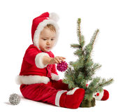Funny baby in Santa Claus clothes  is decorating xmas tree Stock Image