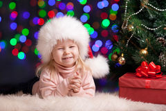 Funny baby in Santa Claus hat on bright festive ba Stock Photo