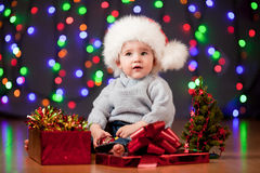 Funny baby in Santa hat on festive background Stock Photo