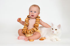 Funny baby sits with bunch of bagels and hugging a cat on white background. Royalty Free Stock Image