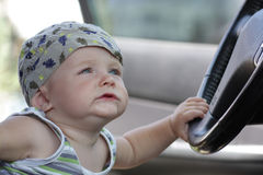 Funny baby sits in car Stock Image