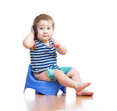 Funny baby sitting on chamber pot with pda Stock Images