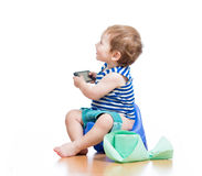 Funny baby sitting on chamber pot with pda Royalty Free Stock Photos