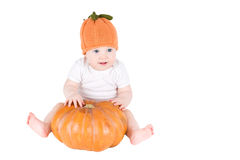 Funny baby sitting next to a pumpkin wearing a knitted pumpkin hat. Isolated on white Royalty Free Stock Image