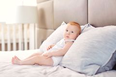 Funny baby is sitting on a pillow on the bed. royalty free stock photo
