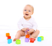 Funny baby sitting playing with colorful toys Royalty Free Stock Photos