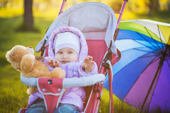 Funny Baby is sitting in stroller on nature Stock Images