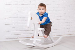 Funny baby sitting on the toy horse Stock Photos
