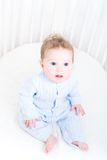 Funny baby sitting in a white round crib Royalty Free Stock Photos