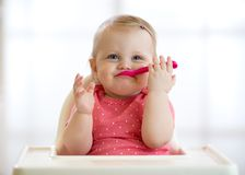 Funny baby with spoon in her mouth. Beautiful child girl sitting in high chair and waiting food. Nutrition for kids Stock Photo
