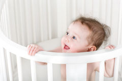 Funny baby standing in a white round crib Stock Photo