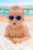 Funny baby in sunglasses on the beach Stock Image