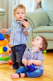 Funny baby toddlers playing toys at home Stock Photos