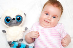 Funny baby with toy. Portrait of a funny baby girl with her lemur soft toy Royalty Free Stock Photos