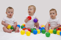 Funny baby triplets smiliing and playing with colorful balls. Studio shot.  Royalty Free Stock Photos