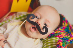 Funny baby trying paper mustache Stock Photography
