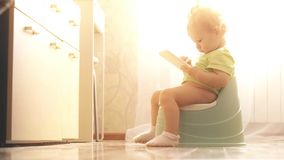 Funny focused baby uses smartphone while sitting on the potty. Funny baby uses smartphone while sitting royalty free stock photos