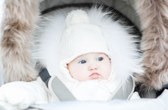 Funny baby in a warm stroller on a cold winter day Royalty Free Stock Photos