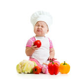 Funny baby weared as cook with vegetables. Funny baby girl weared cook with vegetables Royalty Free Stock Photo