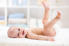 Funny baby weared diaper lying on bed Stock Image