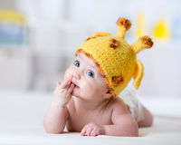 Funny baby weared giraffe hat. Lying on bed in nursery royalty free stock photography