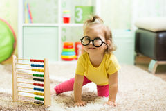 Funny baby weared glasses with counter toy Royalty Free Stock Photos