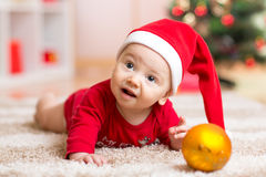 Funny baby wearing Santa hat and suit. Kid boy lying on tummy in front of Christmas tree Royalty Free Stock Images