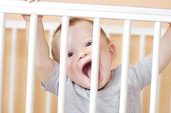 Funny baby in white bed. Funny baby age of 10 months in white bed Royalty Free Stock Photo