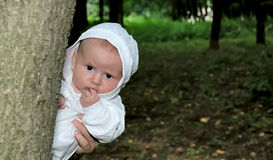 Funny baby in white jumpsuit on nature Royalty Free Stock Photos