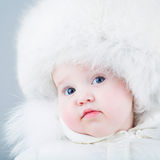 Funny baby in white snow suit and big fur hat Stock Photo