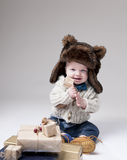 Funny baby in a winter fur hat with gift boxes. Over gray background Royalty Free Stock Image
