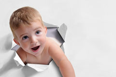 Funny background of a baby coming out of a paper royalty free stock images