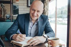 Funny bald businessman sitting at table. Funny bald russian businessman sitting at table royalty free stock photography
