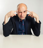 Funny bald businessman trying to think seriously. Man Sitting at desk Royalty Free Stock Photos