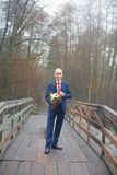 Funny bald groom in a blue suit Stock Photography