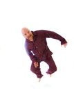 Funny bald man. A funny bald man wearing flannel pajamas jumping in the air Royalty Free Stock Photo