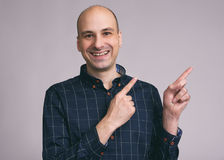 Funny bald man pointing to copy space. Guy smiling Royalty Free Stock Images