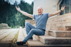 Funny bald man sits on the steps in the Park Stock Photos