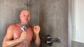 Funny bald middle-aged man washes in the shower and expressively sings