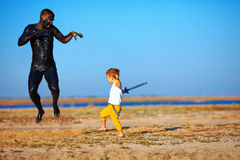 Funny battle of kid with black man Stock Photo