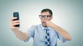 Funny bearded businessman photographing himself on a smartphone. Royalty Free Stock Images