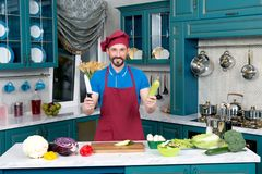 Funny bearded Cook in apron and hat holds knife and zucchini. Funny Chef in apron and hat holds knife and zucchini. Cook holds in hands zucchini and knife on Royalty Free Stock Images